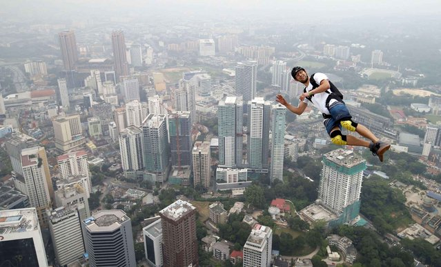 Base jumper Kristian Moxnes of Norway leaps from the 300-meter Open Deck of the Malaysia's landmark Kuala Lumpur Tower during the International Tower Jump in Kuala Lumpur, Friday, September 27, 2013. (Photo by Vincent Thian/AP Photo)