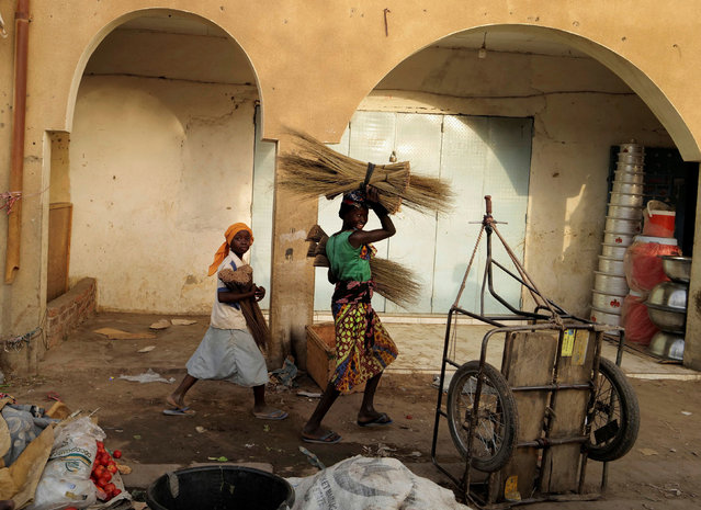 Street vendor girls carry brooms for sale at the market in N'djamena, Chad on April 26, 2021. (Photo by Zohra Bensemra/Reuters)