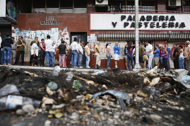 People stand in line to buy bread at a bakery in San Cristobal, February 28, 2014. Annual inflation of more than 56 percent and shortages of basic products ranging from milk and flour to toilet paper and medicines are afflicting all Venezuelans whatever their political convictions. (Photo by Carlos Garcia Rawlins/Reuters)