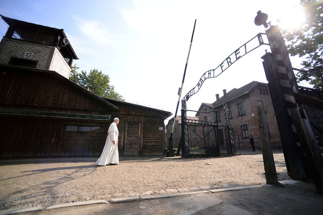 """Pope Francis walks through Auschwitz's notorious gate with the sign """"Arbeit Macht Frei"""" (Work sets you free) during his visit to the former Nazi death camp, Poland, July 29, 2016. (Photo by Filippo Monteforte/Reuters)"""