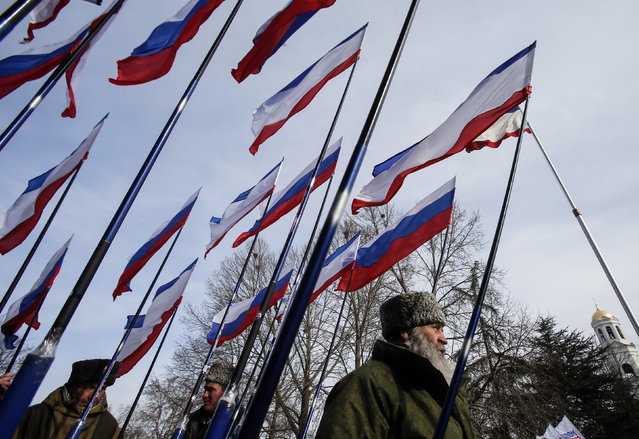Members of pro-Russian self-defense units hold Russian and Crimean flags during a meeting to celebrate the first anniversary of Russia's annexation of Crimea, in central Simferopol March 16, 2015. (Photo by Maxim Shemetov/Reuters)