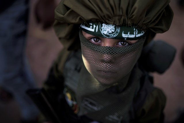 A boy holds a toy rifle as Hamas militants parade at a rally just over a week after a cease-fire was reached in an 11-day war between Hamas and Israel, Sunday, May 30, 2021, in Beit Lahia, northern Gaza Strip. (Photo by Felipe Dana/AP Photo)