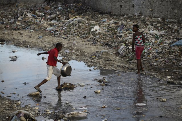 Children cross a polluted canal in Port-au-Prince, Haiti, January 26, 2016. Zika outbreaks have been reported in Haiti. The virus is spread by the Aedes aegypti mosquito, which is notoriously adaptive. The insect thrives in puddles, nooks and crannies common in tropical cities peppered with chaotic and unplanned neighbourhoods, where rainwater, open sewers and litter offer ample habitat. (Photo by Andres Martinez Casares/Reuters)