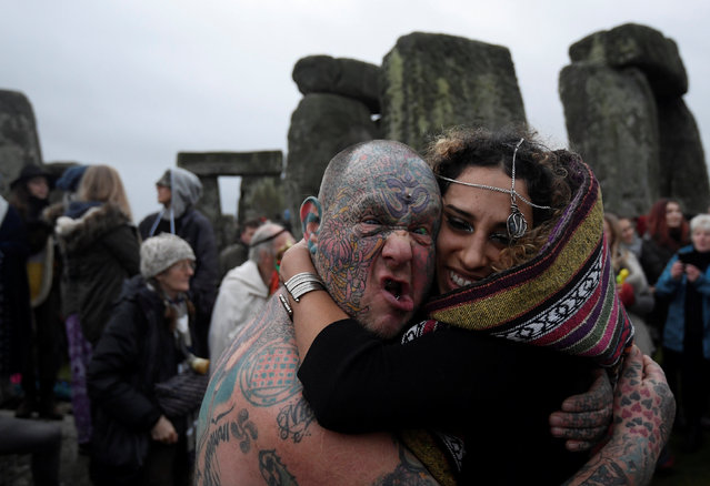 Visitors and revellers react amongst the prehistoric stones of the Stonehenge monument at dawn on Winter Solstice, near Amesbury in south west Britain, December 21, 2016. (Photo by Toby Melville/Reuters)