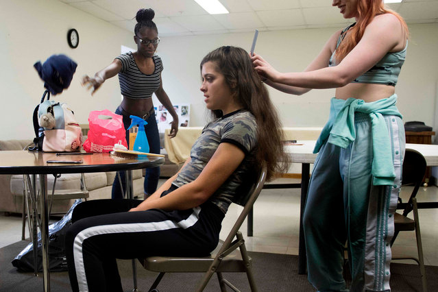 Professional wrestler Gia Scott (L) throws some off her gear on a table as her opponent for the Autumn Armageddon 2018, professional wrestler Aria Palmer (C), gets her hair done in their makeshift dressing room at a firehouse in Galena, Maryland on October 6, 2018. (Photo by Jim Watson/AFP Photo)