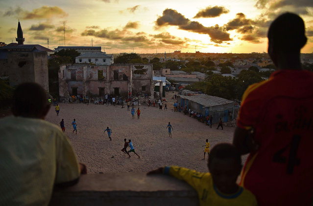 Somalis play football as the sun sets in Mogadishu on March 24, 2015. (Photo by Carl De Souza/AFP Photo)