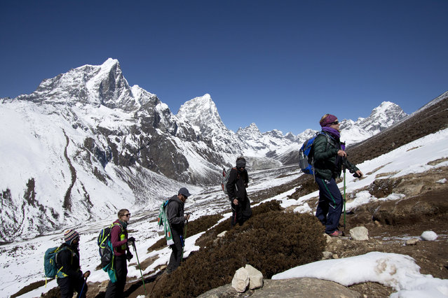 In this Wednesday, March 18, 2015 photo, trekkers take an acclimatization hike to Nagarzhang peak above Dingboche valley on the way to Everest base camp, Nepal. (Photo by Tashi Sherpa/AP Photo)