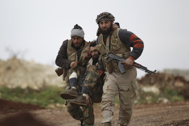 Fighters from Suqour al-Sham Brigade, which is part of the Free Syrian Army, carry a wounded member of their brigade during what activists said were clashes with forces of Syria's President Bashar al-Assad, in the al-Arbaeen mountain area of western Idlib January 30, 2015. (Photo by Khalil Ashawi/Reuters)