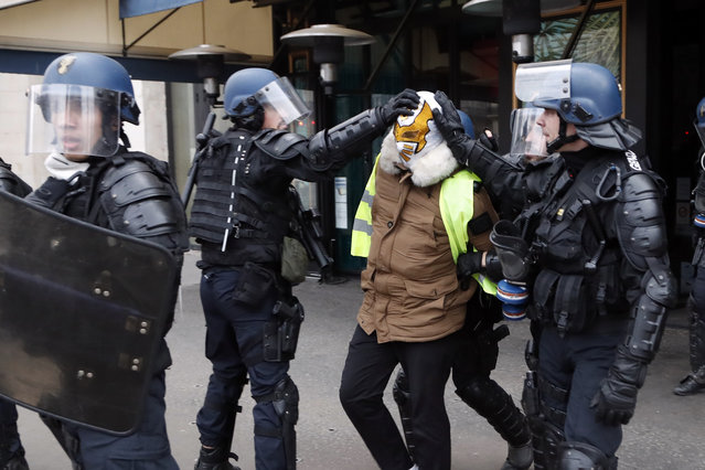 A demonstrator is lead away by riot police after being arrested during clashes, in Paris, France, Saturday, December 8, 2018. (Photo by Thibault Camus/AP Photo)
