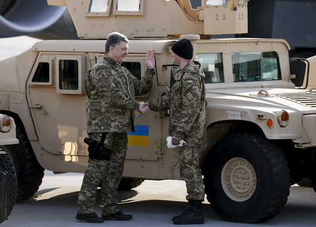 Ukraine's President Petro Poroshenko (L) welcomes a serviceman during a welcome ceremony for first plane from United State with non-lethal aid including ten Humvee vehicles to Ukraine at Borispol airport near Kiev, March 25, 2015. The United States send additional non-lethal aid to Ukraine, including unarmed drones and Humvee vehicles, a U.S. defense official said on March 11. (Photo by Gleb Garanich/Reuters)