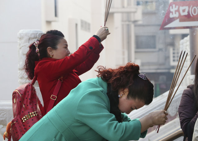 Visitors hold joss sticks as they offer prayer at a temple in China Town in Yokohama, near Tokyo, Monday, February 8, 2016.(Photo by Koji Sasahara/AP Photo)