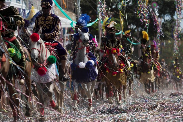 Revellers participate in the traditional Carnival on horseback, a tradition dating back to the 18th century, in Bonfim, Brazil, February 8, 2016. (Photo by Roosevelt Cassio/Reuters)