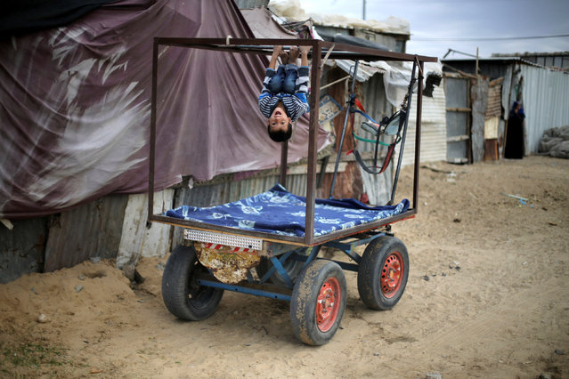 A Palestinian boy plays on a cart outside his family's shanty in Khan Younis, in the southern Gaza Strip November 30, 2016. (Photo by Ibraheem Abu Mustafa/Reuters)