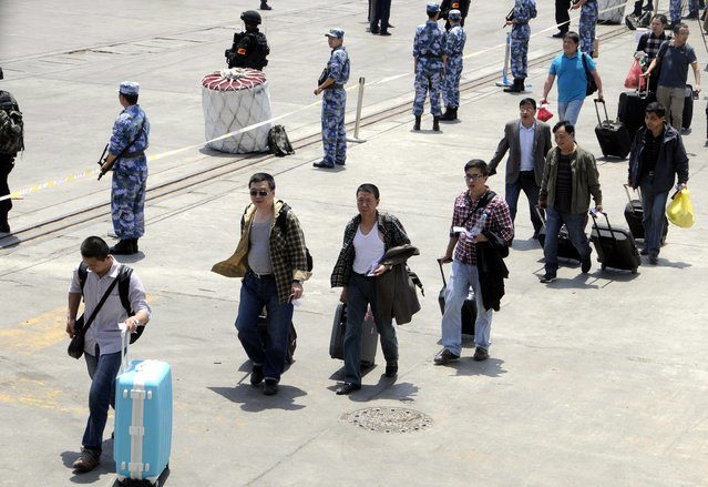 Chinese soldiers (L) keep watch as Chinese people prepare to depart for their country during an evacuation from Yemen at a sea port in the western port city of Hodeidah, Yemen, 30 March 2015. Chinese Defense Ministry said on 30 March it was sending a naval fleet to help evacuate its citizens from Yemen as the conflict worsens. The government made the decision after Saudi Arabia launched airstrikes on its southern neighbor last week. (Photo by EPA/Stringer)