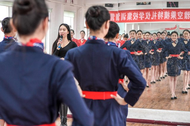 Students attend a stewardess skill training for the upcoming 2017 entrance examination for art majors in colleges in Luoyang, central China's Henan Province, January 4, 2017. The instructor issues her commands though a microphone as her students check their posture in a mirror. (Photo by Li Bo/Xinhua/Barcroft Images)