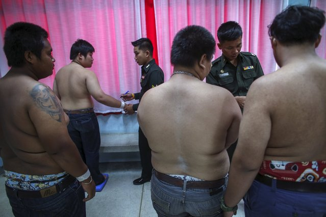 Young men wait to be weighed during an army draft held at a school in Bang Na in Bangkok April 3, 2015. (Photo by Athit Perawongmetha/Reuters)