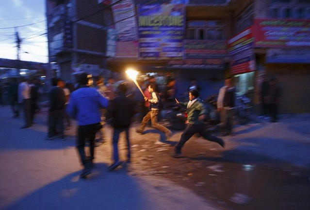 A protester tries to run from the riot police personnel (unseen) trying to stop the torch rally in Kathmandu April 6, 2015. (Photo by Navesh Chitrakar/Reuters)