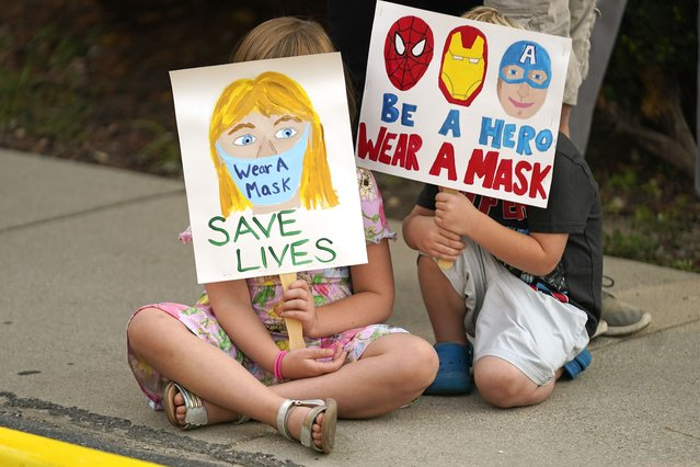 Lucie Phillips, 6, and her brother David Phillips, 3, join parents and students during a rally at Utah State School Board Office calling for mask mandate Friday, August 6, 2021, in Salt Lake City. The school year is days away for many kids in Utah and public health experts are worried about whether kids too young to get vaccinated will stay safe in school amid a wave of coronavirus cases. (Photo by Rick Bowmer/AP Photo)