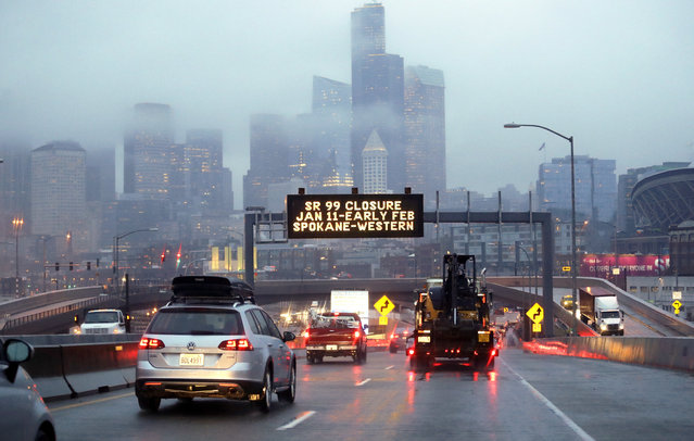 In this photo taken Thursday, January 3, 2019, rush hour northbound Highway 99 traffic backs-up while heading toward the Alaskan Way Viaduct just ahead as a sign overhead advises of an upcoming closure of the roadway in Seattle. The double-decker highway along Seattle's waterfront is set to shut down for good Friday, Jan. 11, ushering in what officials say will be one of the most painful traffic periods in the city's history. The 65-year-old viaduct is being replaced by a four-lane Highway 99 tunnel, scheduled to open several weeks after the viaduct's closure. (Photo by Elaine Thompson/AP Photo)