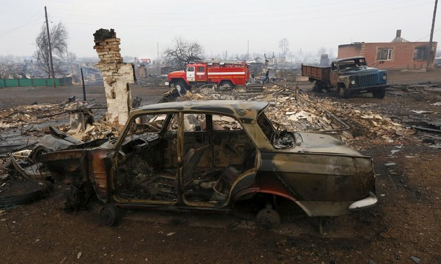 Burnt vehicles are seen in the settlement of Shyra, damaged by recent wildfires, in Khakassia region, April 13, 2015. (Photo by Ilya Naymushin/Reuters)