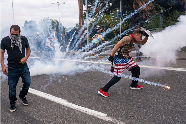 Far-right extremists react to an exploding firework thrown by left-wing counter protesters on August 22, 2021 in Portland, Oregon. The Proud Boys and other far-right extremists fought with anti-fascist activists in Portland on the anniversary of a similar fight in 2020. (Photo by Nathan Howard/Getty Images)