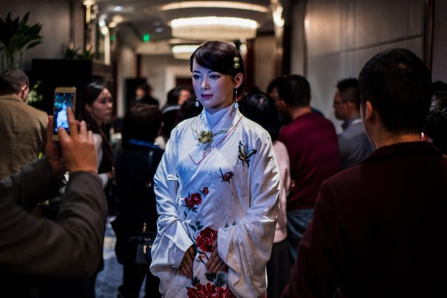 """People take pictures of humanoid robot Jia Jia, created by a team of engineers from the University of Science and Technology of China, following a presentation at a conference in Shanghai on January 9, 2017. """"Jia Jia"""" can hold a simple conversation and make specific facial expressions when asked, and her creator believes the eerily life- like robot heralds a future of cyborg labour in China. Billed as China' s first human- like robot, Jia Jia was first trotted out last year by a team of engineers at the University of Science and Technology of China. (Photo by Johannes Eisele/AFP Photo)"""