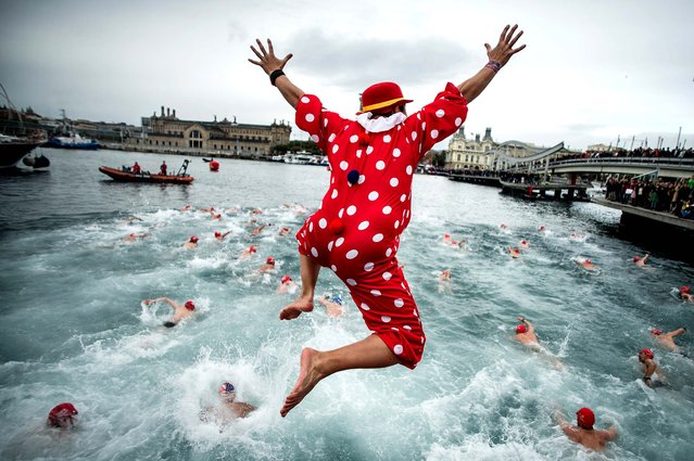 A competitor jumps into the sea during the 104th Barcelona Traditional Christmas Swimming Cup at the Old Harbour of Barcelona, on December 25, 2013. The Copa Nadal is organized by the Barcelona Swimming Club and involves competitors swimming across some 200 meters of water in the harbor. Launched in 1908, the event has only been suspended three times, when the Spanish Civil War interrupted proceedings between 1936 and 1938. (Photo by David Ramos/Getty Images)