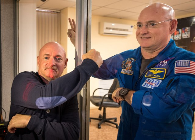 Retired NASA Astronaut Mark Kelly, left, fist pumps his identical twin brother, NASA Astronaut Scott Kelly through glass as Scott Kelly and fellow crew mates, Russian cosmonauts Gennady Padalka, and Mikhail Kornienko of the Russian Federal Space Agency (Roscosmos) participate in a press conference while in quarantine Thursday, March 26, 2015, at the Cosmonaut Hotel in Baikonur, Kazakhstan. Mark Kelly, who flew four space shuttle missions and commanded the final flight of space shuttle Endeavour, will participate in biomedical studies on the ground while his twin is on board the orbiting laboratory. (Photo by /Bill Ingalls/NASA)