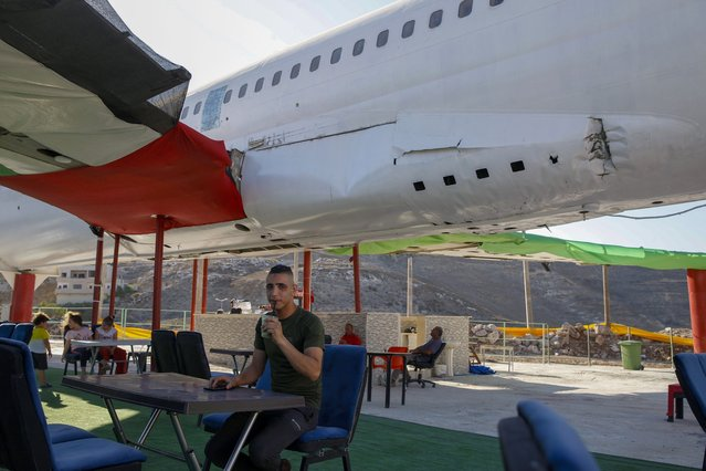 """Palestinians visit a Boeing 707 aircraft after it was converted to a cafe restaurant, in Wadi Al-Badhan, near the West Bank city of Nablus, Wednesday, August 11, 2021. The Palestinian territory has no civilian airport and those who can afford a plane ticket must catch their flights in neighboring Jordan. After a quarter century of effort, twins brothers, Khamis al-Sairafi and Ata, opened the """"Palestinian-Jordanian Airline Restaurant and Coffee Shop al-Sairafi"""" on July 21, 2021, offering people an old airplane for customers to board. (Photo by Majdi Mohammed/AP Photo)"""