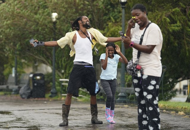 Tony Hilliard, left, and his family expose themselves to the elements as Hurricane Ida begins to make landfall, Sunday, August 29, 2021, in New Orleans, La. (Photo by Eric Gay/AP Photo)