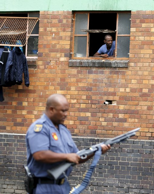 A man looks out of a hostel window as a police officer walks past in Johannesburg, April 17, 2015. (Photo by Siphiwe Sibeko/Reuters)
