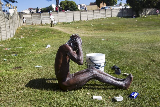 "A foreign man bathes on a sports field adjacent to a camp for those affected by anti-immigrant violence in Chatsworth north of Durban, April 21, 2015.  South Africa deployed the army on Tuesday in ""volatile areas"" to curb a wave of anti-immigrant violence that has killed at least seven people this month, the defence minister said. (Photo by Rogan Ward/Reuters)"