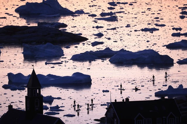 People ride stand-up paddle boards past floating ice and icebergs in Disko Bay on September 02, 2021 in Ilulissat, Greenland. Greenland in 2021 is experiencing one of its biggest ice-melt years in recorded history. Scientists studying the Greenland Ice Sheet observed rainfall on the highest point in Greenland for the first time ever in August. Researchers from Denmark estimated that in July of this year, enough ice melted on the Greenland Ice Sheet to cover the entire state of Florida with two inches of water. The observations come on the heels of the recent United Nations report on global warming which stated that accelerating climate change is driving an increase in extreme weather events. (Photo by Mario Tama/Getty Images)