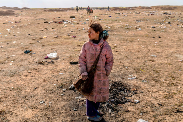 A girl stands alone as women and children evacuated from the Islamic State (IS) group's embattled holdout of Baghouz arrive at a screening area held by the US-backed Kurdish-led Syrian Democratic Forces (SDF), in the eastern Syrian province of Deir Ezzor, on March 5, 2019. More than 7000 people, mostly women and children, have fled the shrinking pocket over the past days, as US-backed forces press ahead with an offensive to crush holdout jihadists. (Photo by Bulent Kilic/AFP Photo)