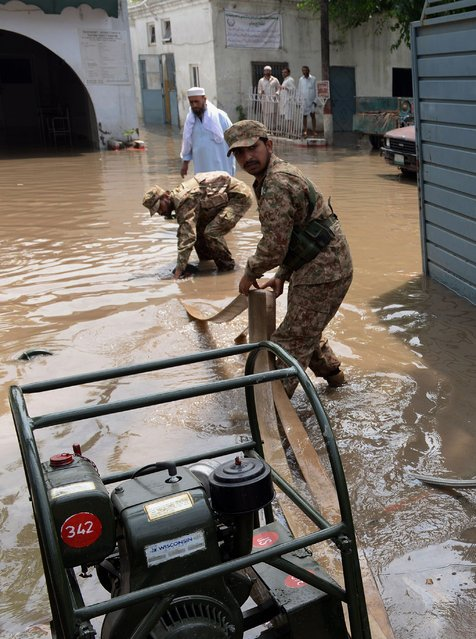 "Pakistani soldiers pump rain water from a residential area following heavy rain and winds in Peshawar on April 27, 2015. A severe storm in northwest Pakistan, dubbed a ""mini-cyclone"", has killed 44 people and injured more than 200, officials said, raising their previous death toll. (Photo by A. Majeed/AFP Photo)"