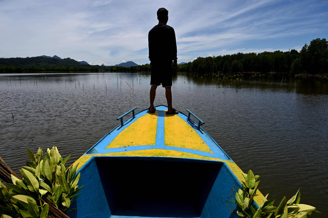 A student prepares to plant mangroves in Calang, Indonesia's Aceh province on September 15, 2021. (Photo by Chaideer Mahyuddin/AFP Photo)