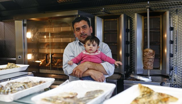 "Zohair Baktarah, 34, poses for a photograph with his son Amneh at his workplace, Amneh Grill, in the London constituency of Brent Central, Britain, April 3, 2015.  Baktarah was born in Syria and said: ""I love England and David Cameron"". (Photo by Eddie Keogh/Reuters)"