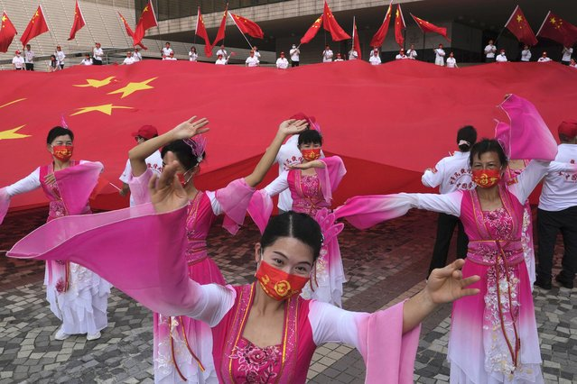 Dancers preform in front of a huge Chinese national flag during a ceremony to mark China's 72nd National Day in Hong Kong Friday, October 1, 2021. (Photo by Vincent Yu/AP Photo)