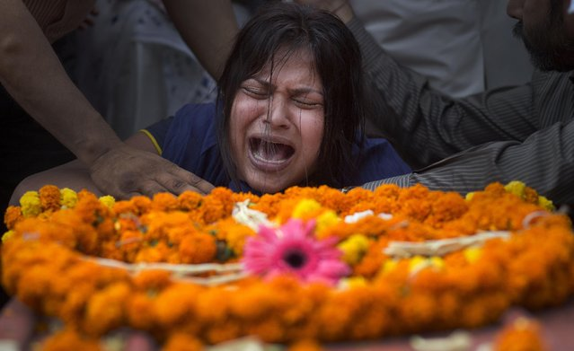 An Indian girl cries near the coffin of her mother Hema Prabha Saikia, a victim of Saturday's earthquake in Nepal, in Gauhati, India, Wednesday, April 29, 2015. The bodies of six women victims arrived in Gauhati on Wednesday. (Photo by Anupam Nath/AP Photo)