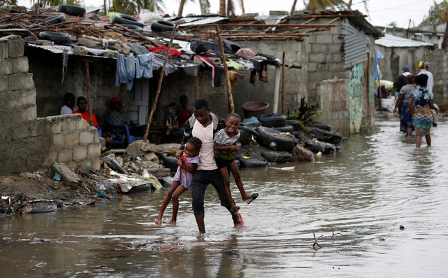 A man carries his children after Cyclone Idai at Praia Nova, in Beira, Mozambique, March 23, 2019. (Photo by Siphiwe Sibeko/Reuters)