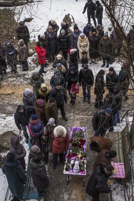 Relatives and friends of Elena Volkova, a victim of shelling, grieve at her funeral in Avdiivka, eastern Ukraine, Monday, February 6, 2017. Fighting between government forces and Russia-backed separatist rebels has escalated over the past week in eastern Ukraine, killing at least 36 people, including civilians, and wounding dozens. (Photo by Evgeniy Maloletka/AP Photo)