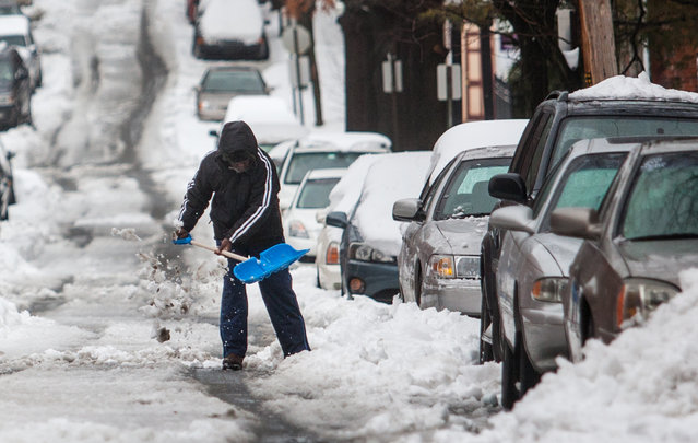 A man shovels out his car along Ninth Street in Wilmington, Del. on Thursday afternoon, February 13, 2014. The city saw nearly a foot of snow fall over night, and heavy sleet in the morning, making travel difficult. (Photo by Kyle Grantham/AP Photo/The Wilmington News-Journal)