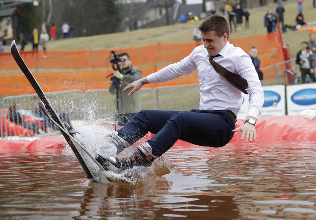 """A Belarusian snowboarder takes part in the comic competition """"Californication 9.0"""" at an entertainment center in the town of Logoisk, 40 km (25 miles) north of Minsk, Belarus, Sunday, April 7, 2019. Eighty participants in the costumes skied from the springboard and jumped into the icy water celebrating the end of winter. (Photo by Sergei Grits/AP Photo)"""
