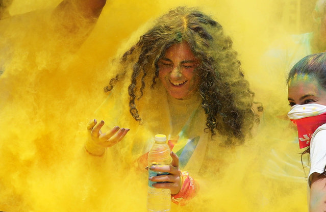 A girl is covered in yellow powder during Egypt's first Color Run in Giza, Egypt on April 13, 2019. (Photo by Mohamed Abd El Ghany/Reuters)