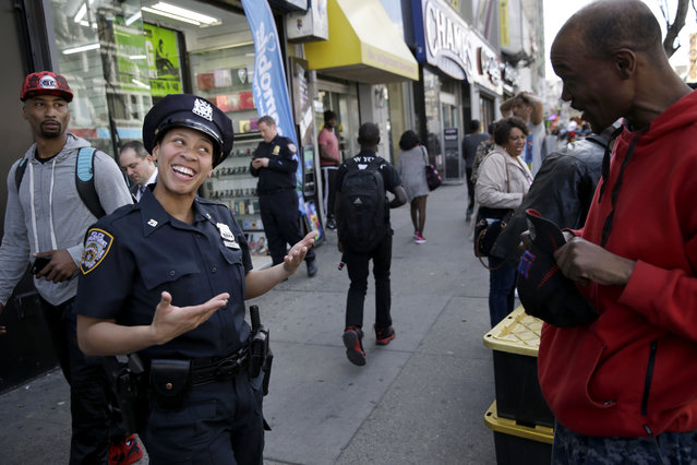 Police officer Lanora Moore talks with a man on 125th Street in the Harlem section of New York, Wednesday, April 29, 2015. (Photo by Seth Wenig/AP Photo)
