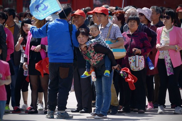 A family (C) looks on after visiting the Forbidden City in Beijing on May 3, 2015. (Photo by Wang Zhao/AFP Photo)