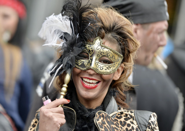 "A woman smiles behind her mask when tens of thousands revelers dressed in carnival costumes celebrate the start of the street-carnival on the so called ""Old Women's Day"" in the party capital Cologne, Germany, Thursday, February 27, 2014. (Photo by Martin Meissner/AP Photo)"