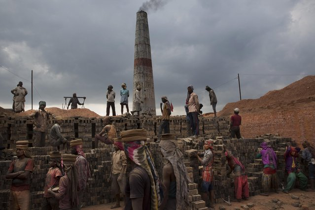 In this Wednesday, May 13, 2015 photo, Indian and Nepalese laborers work at a brick factory in Bhaktapur, Nepal. (Photo by Bernat Amangue/AP Photo)