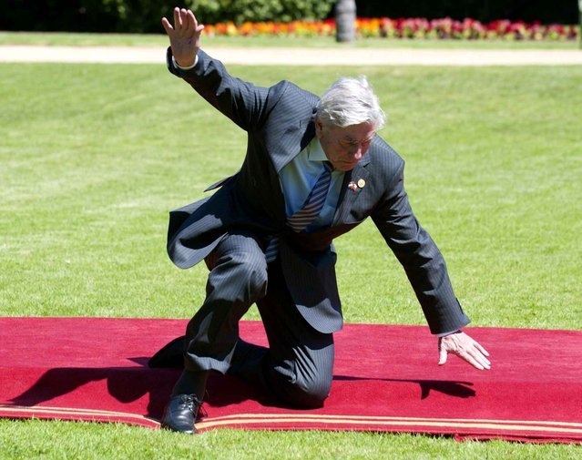 Former Prime Minister of the Netherlands Ruud Lubbers falls after tripping on the red carpet as he arrives to the Cerro Castillo presidential palace for lunch with other visiting dignitaries in Vina del Mar, Chile on March 11, 2014. Lubbers is in Chile to attend the inauguration ceremony of Chilean President Michelle Bachelet. (Photo by Francesco Degasperi/AFP Photo)