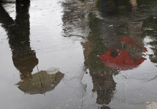 People are reflected in a puddle as they walk carrying umbrellas in Milan, Italy, Monday, April 27, 2015. (Photo by Antonio Calanni/AP Photo)